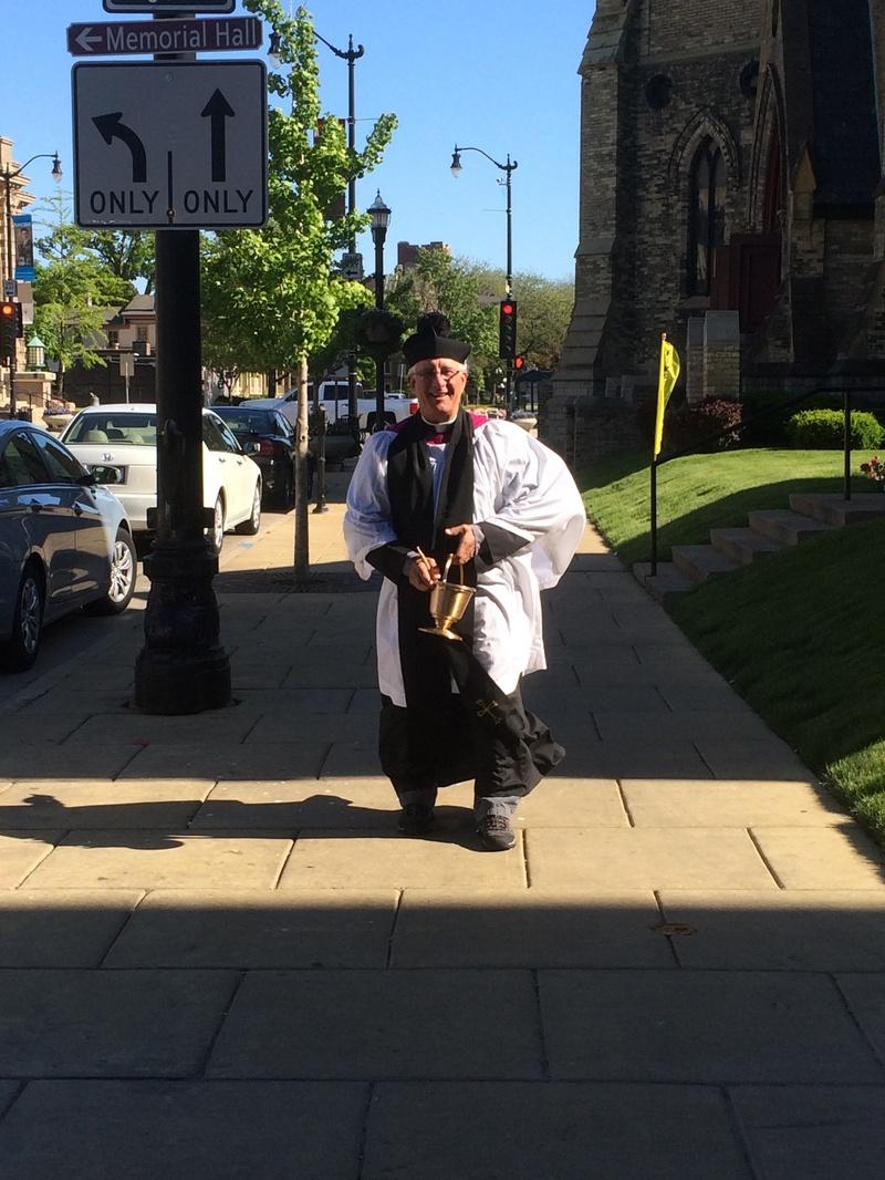 """Fr. Lambert giving """"Blessings on-the-go"""" along Main Street"""